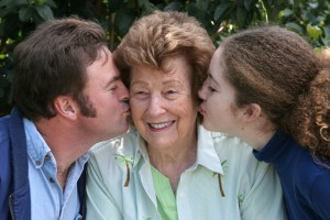 A sweet grandmother receiving kisses from her family.